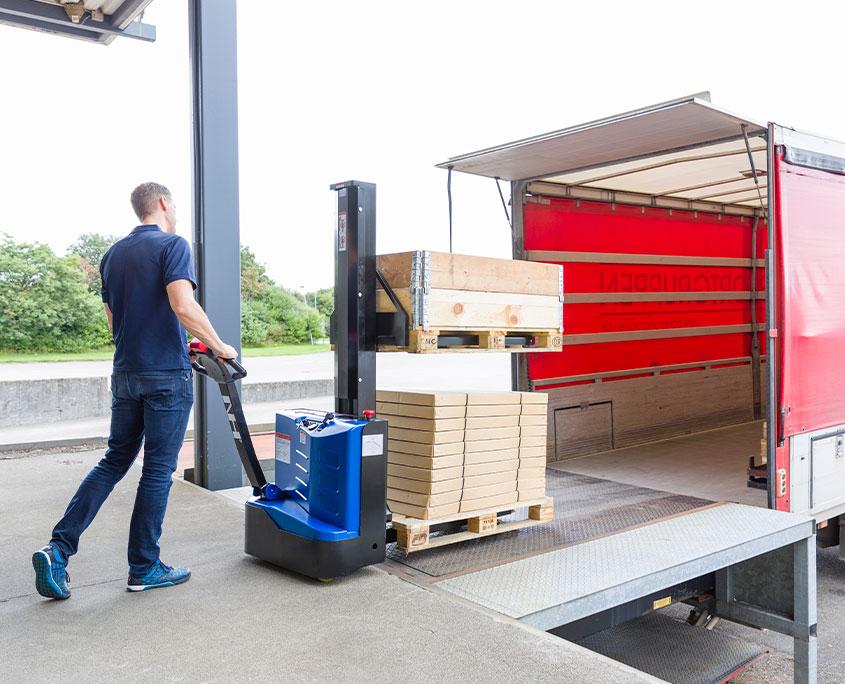 Elektrisk palleløfter læsser varer på lastbil